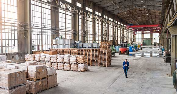 Man in suit walking through warehouse